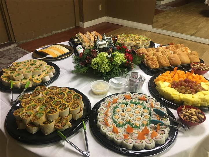 Variety of platters on table - wraps, sandwiches, sushi, fruit