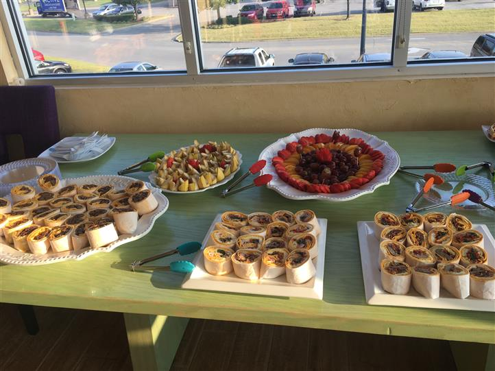 Variety of small wraps and fruit platter on table