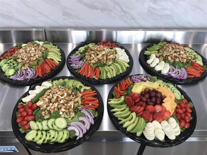 Variety of platters with avocados, eggs, strawberries, red grapes, cantaloupe, pineapple, peppers, cherry tomatoes, onions