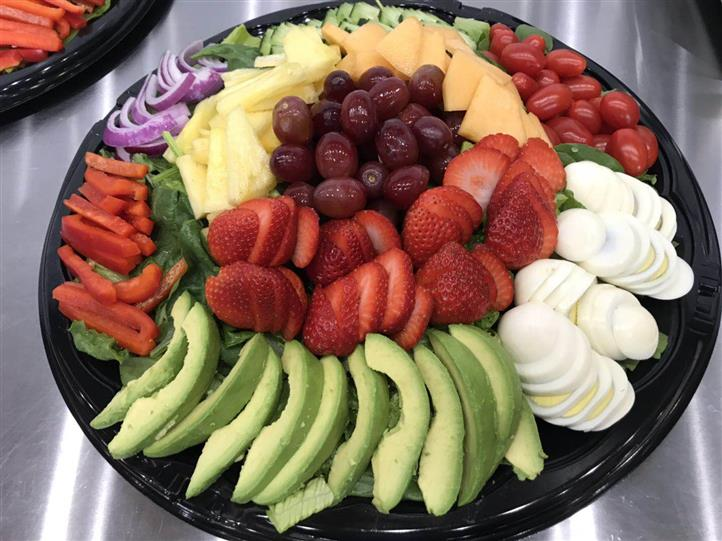 Platter with avocados, eggs, strawberries, red grapes, cantaloupe, pineapple, peppers, cherry tomatoes, onions
