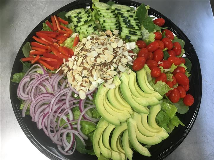 Platter with avocados, onions, almonds, peppers, cherry tomatoes, cucumbers