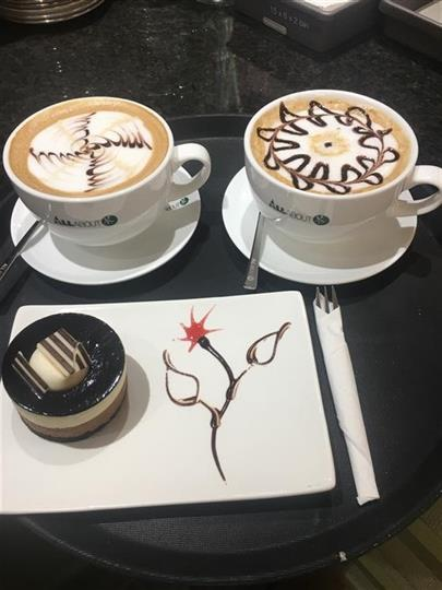 Cafe lattes with designs and dessert on pdish