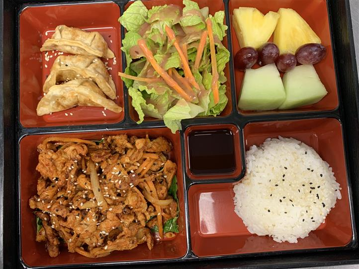Bento box Served with fried dumpling, salad, seasonal fruits, seasoned chicken and steamed rice