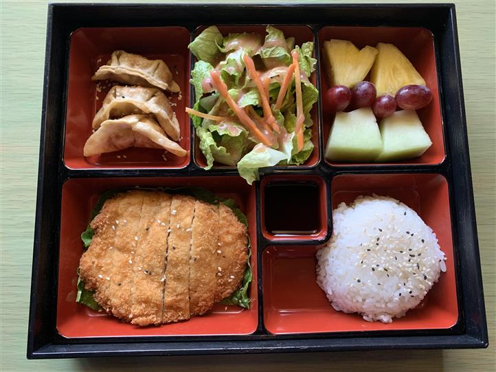 Bento box Served with fried dumpling, salad, seasonal fruits, crispy chicken and steamed rice