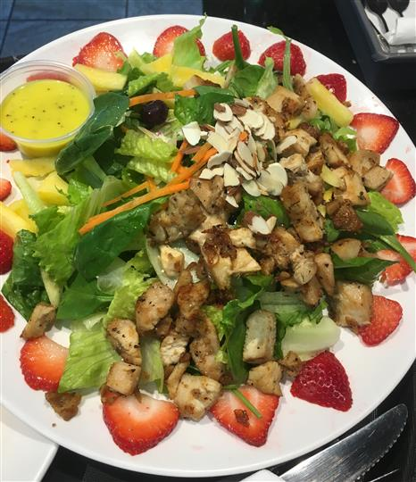 Strawberry poppy seed chicken salad. Grilled or crispy chicken, strawberries, pineapple, blueberries, almonds, carrots on a bed of spinach, romaine lettuce, and feta cheese. Served with poppy seed dressing.
