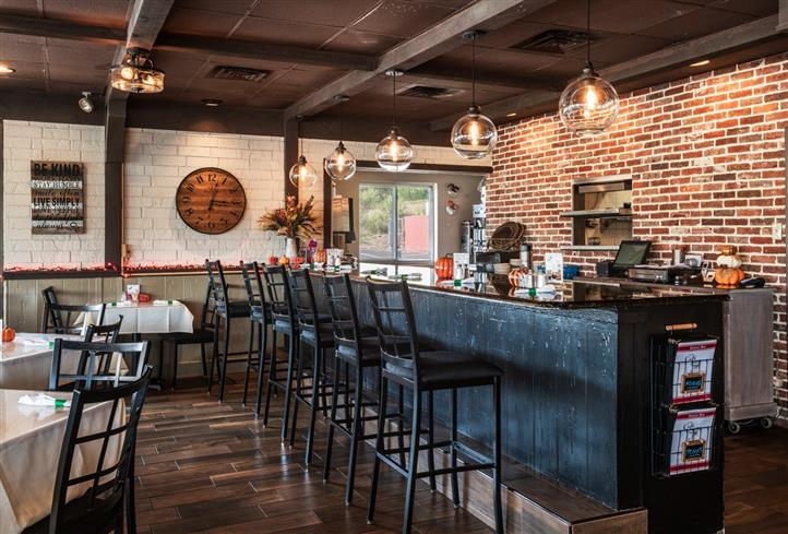 Bar area with high stools, wood bar and brick walls