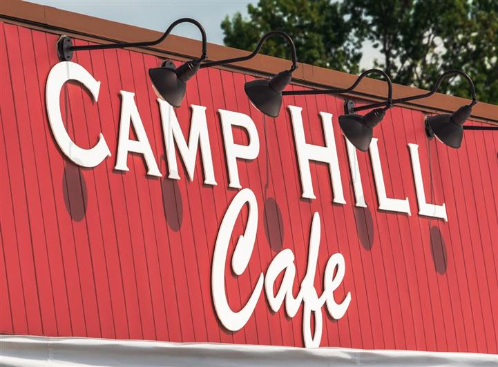 Camp Hill Cafe sign on storefront under goose neck light fixtures
