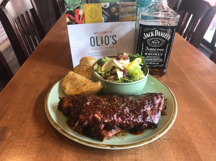 bbq plate with a side of house salad with a bottle of jack daniels whiskey