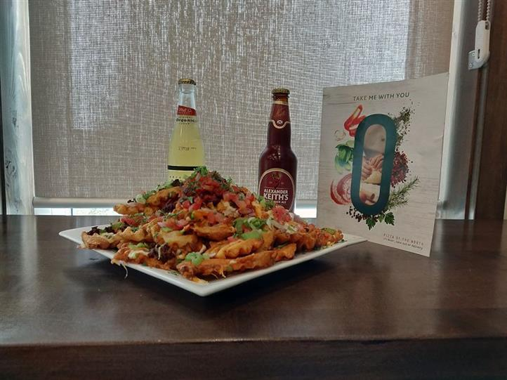 loaded french fries on a plate with bottled beer