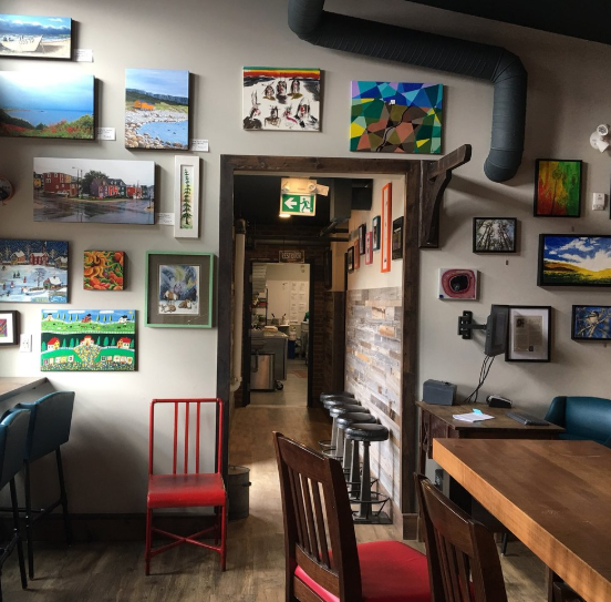 interior of olios pizzeria with artwork on the walls.