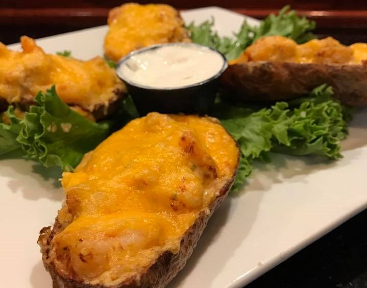 Potato skins with bacon and cheese on top with a side of sour cream