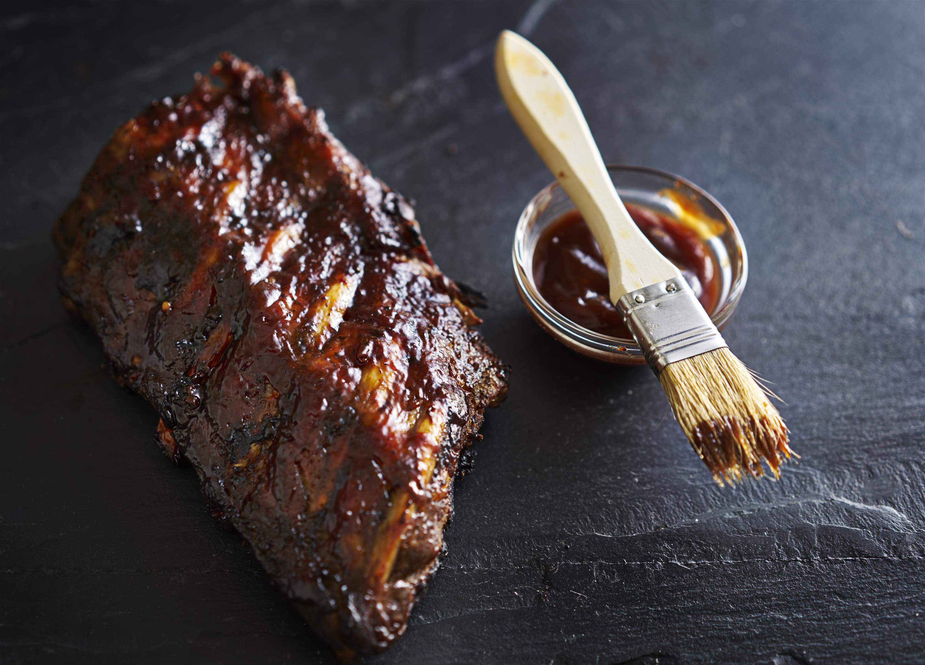bbq ribs with a side of sauce and a brush