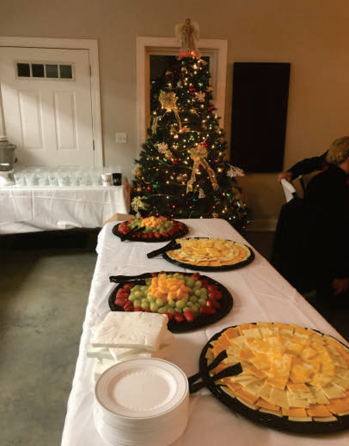 buffet table with assortment of food on round trays with plates and napkins. a decorated christmas tree is in the background.
