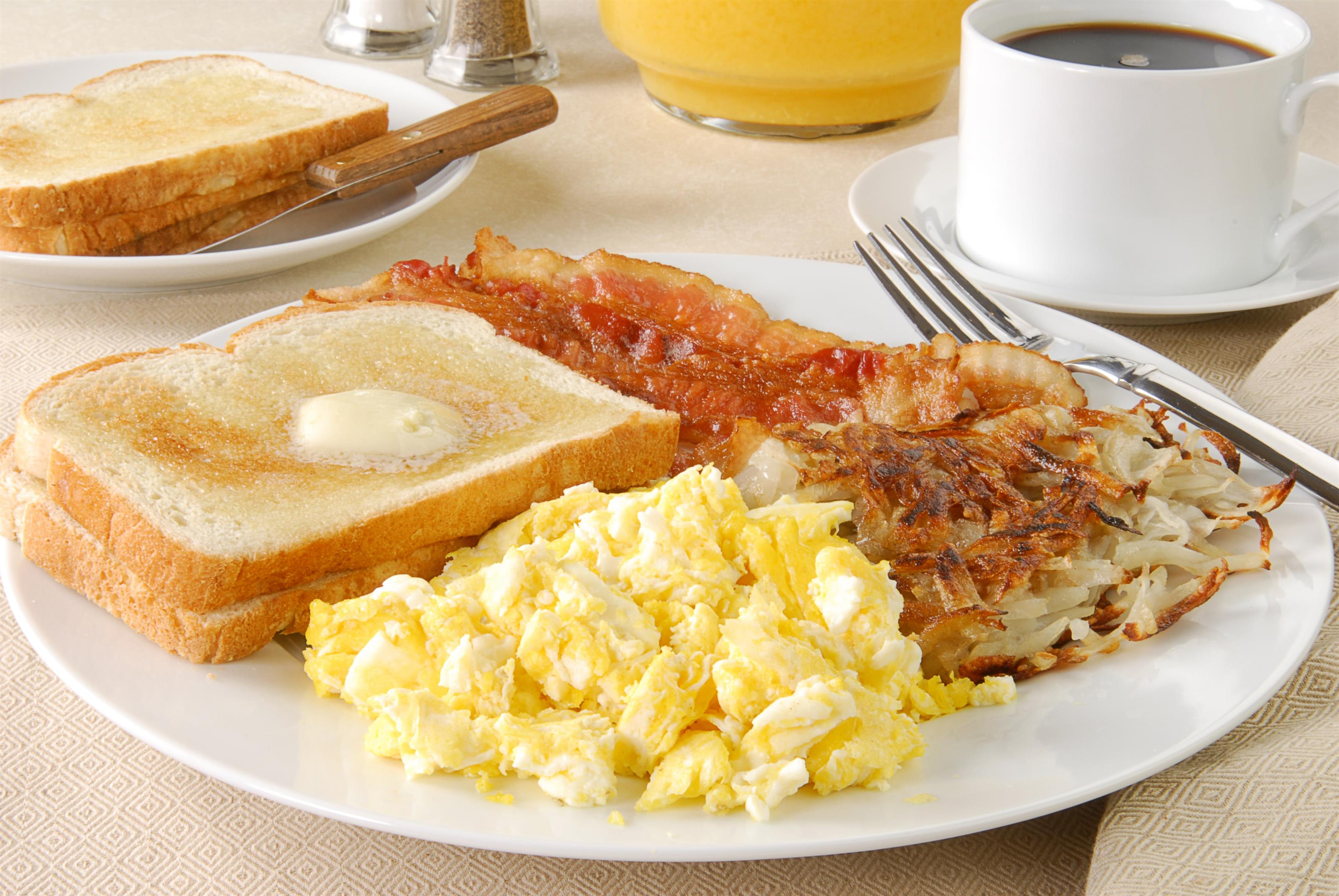 Plate of scrambled eggs, toast, hash browns, bacon in front of coffee cup and orange juice