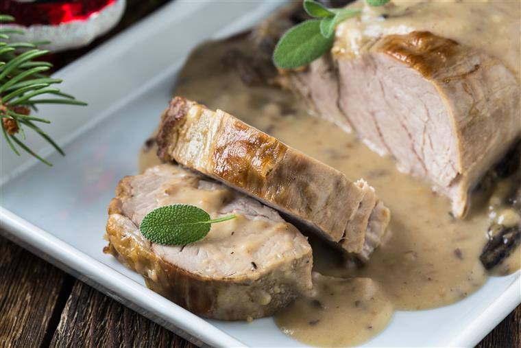 Delicious roast pork fillet with mushroom sauce on a white plate for holiday
