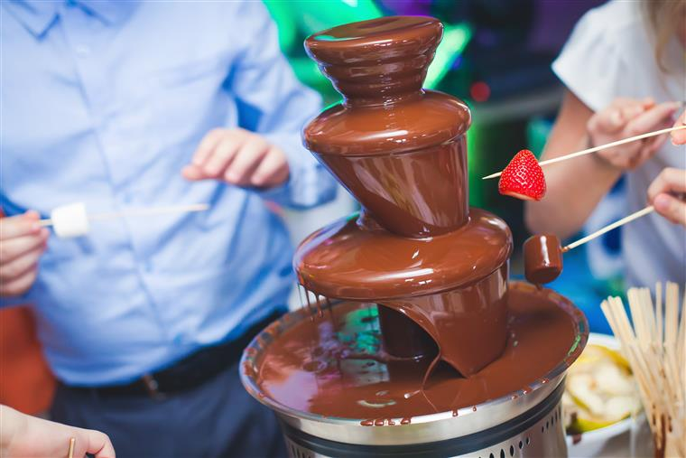 Chocolate Fountain with people dipping fruit and marshmallows