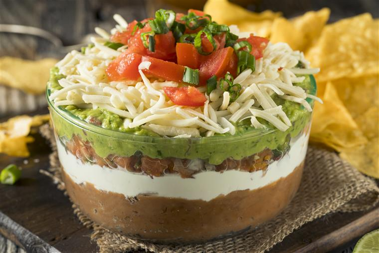 seven layer dip with refried beans, guacamole, tomatoes, sour cream, black olives, shredded cheese, cilantro and green onions. Served with tortilla chips.