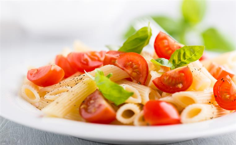Pasta topped with basil, tomatoes.
