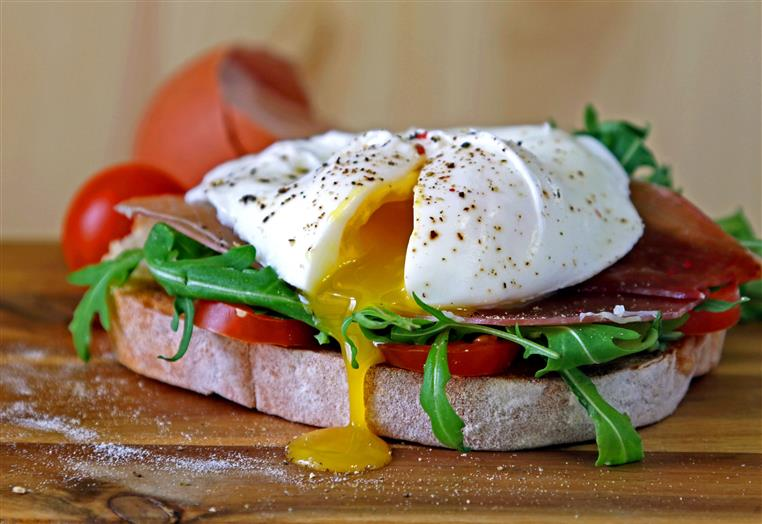 sandwich with Parma ham, arugula, tomato and poached egg