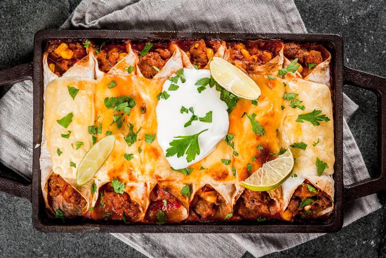 Traditional dish of spicy beef enchiladas with corn, beans, tomato. On a baking tray, on a black stone background.