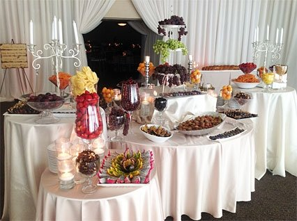 Covered tables with variety of fruits and appetizers