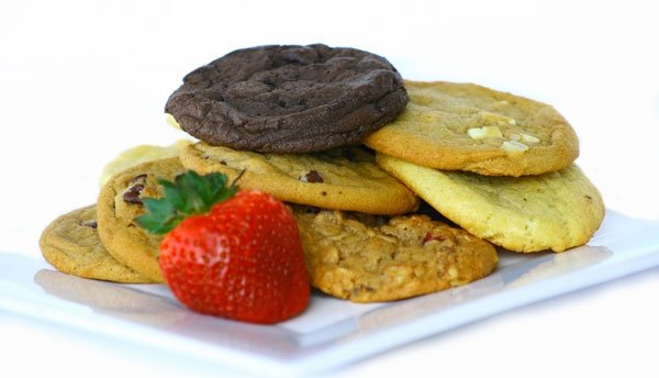 Variety of cookies on dish next to strawberry