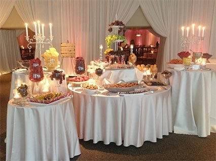 assorted covered tables with assorted desserts under tent