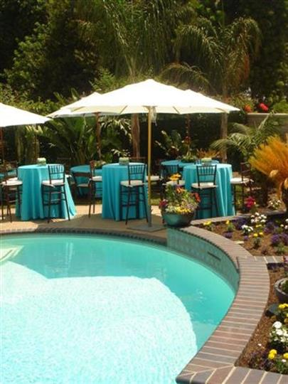 Outdoor seating under umbrellas next to pool