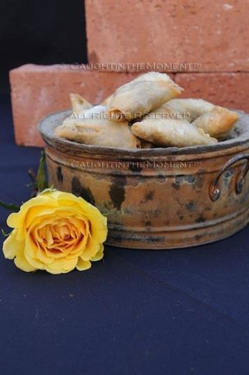 Pastries in fancy container on table next to bricks and flower