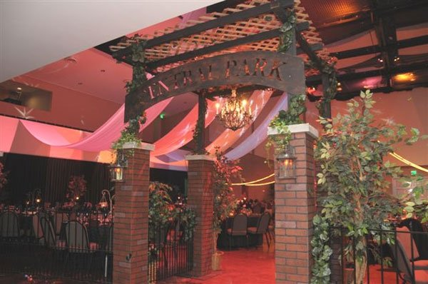 Gated dining area with brick columns and central park sign on arch