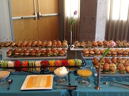Display of sliders with assorted cheeses, vegetables and dips