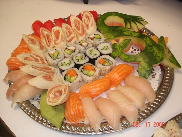 Assorted sushi, sashimi and wraps on decorative dish.