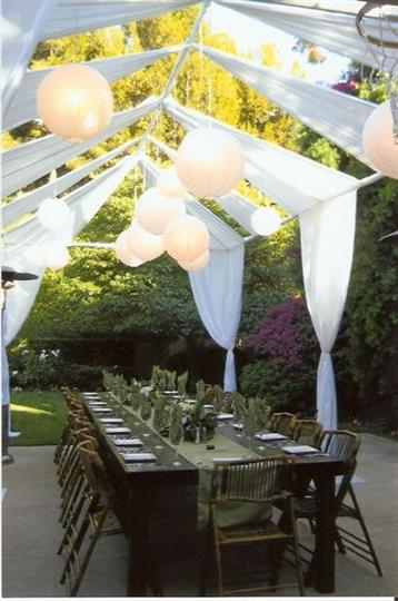 Outdoor wood table with placesettings under archway with balloons