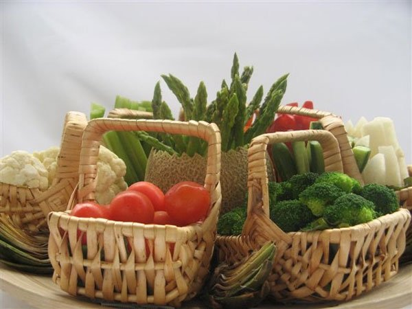 wicker baskets filled with assorted vegetables around canteloupe filled with asparagus.