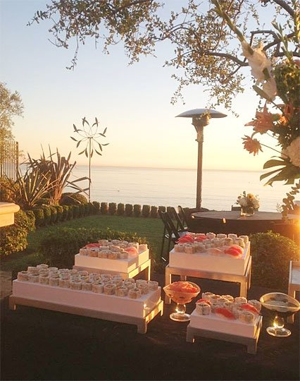 Outdoor catering setup near the water with food on tables