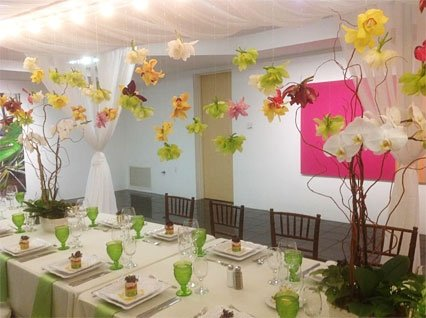 Table with placesettings in room with flower decorations hanging from ceiling