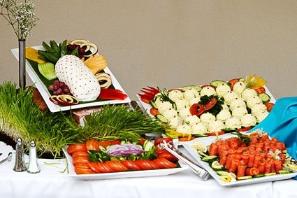 Assorted catering spreads with vegetables, salmon, cheeses.