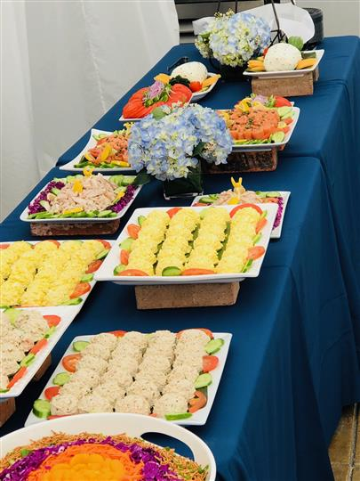 Tuna salad and assorted spreads on dishes garnished with cucumbers and tomatoes