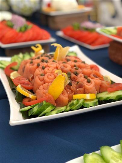 Salmon and capers surrounded by cucumbers, lemons, tomatoes