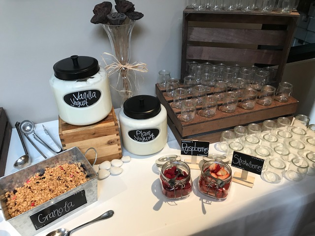 Yogurt station with granola and fruit options next to shotglasses.