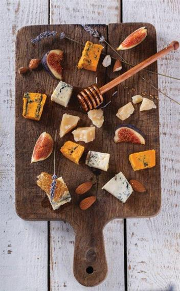 tray of assorted cheeses and nuts with a wood background