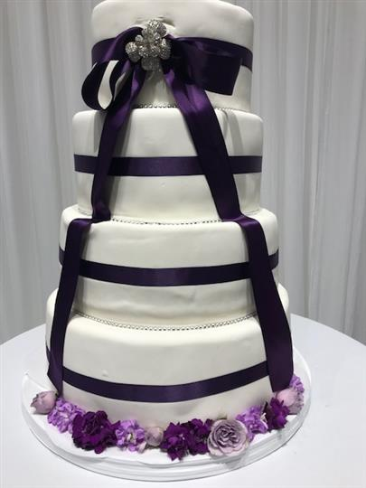 Multi tiered wedding cake with ribbons and flowers