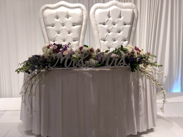 two large chairs behind Mr & Mrs sign on table covered with flowers