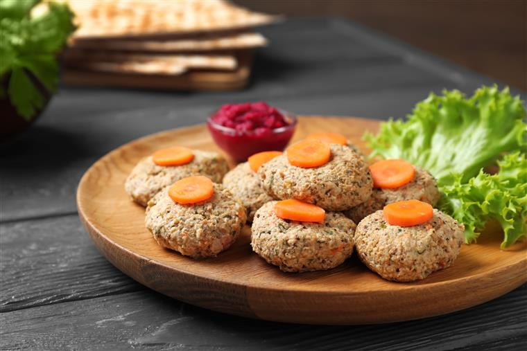 Plate of traditional Passover (Pesach) gefilte fish on wooden table, closeup