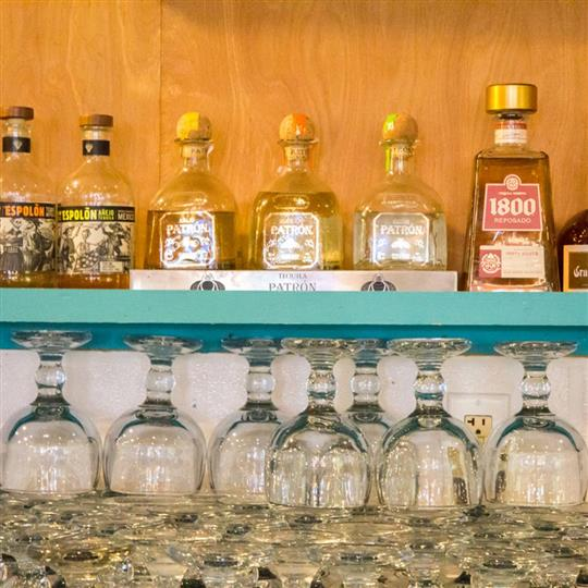 patron bottles being displayed with cocktail glasses