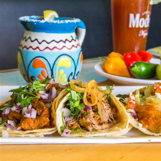 assorted soft shell tacos on a plate with a mixed drink on the side