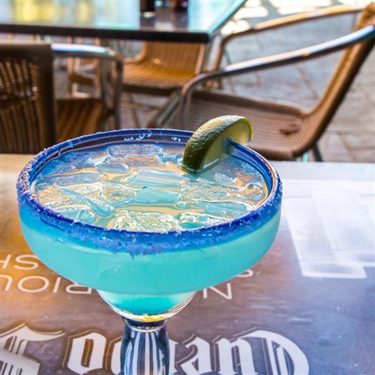 blue cocktail drink with lime wedge