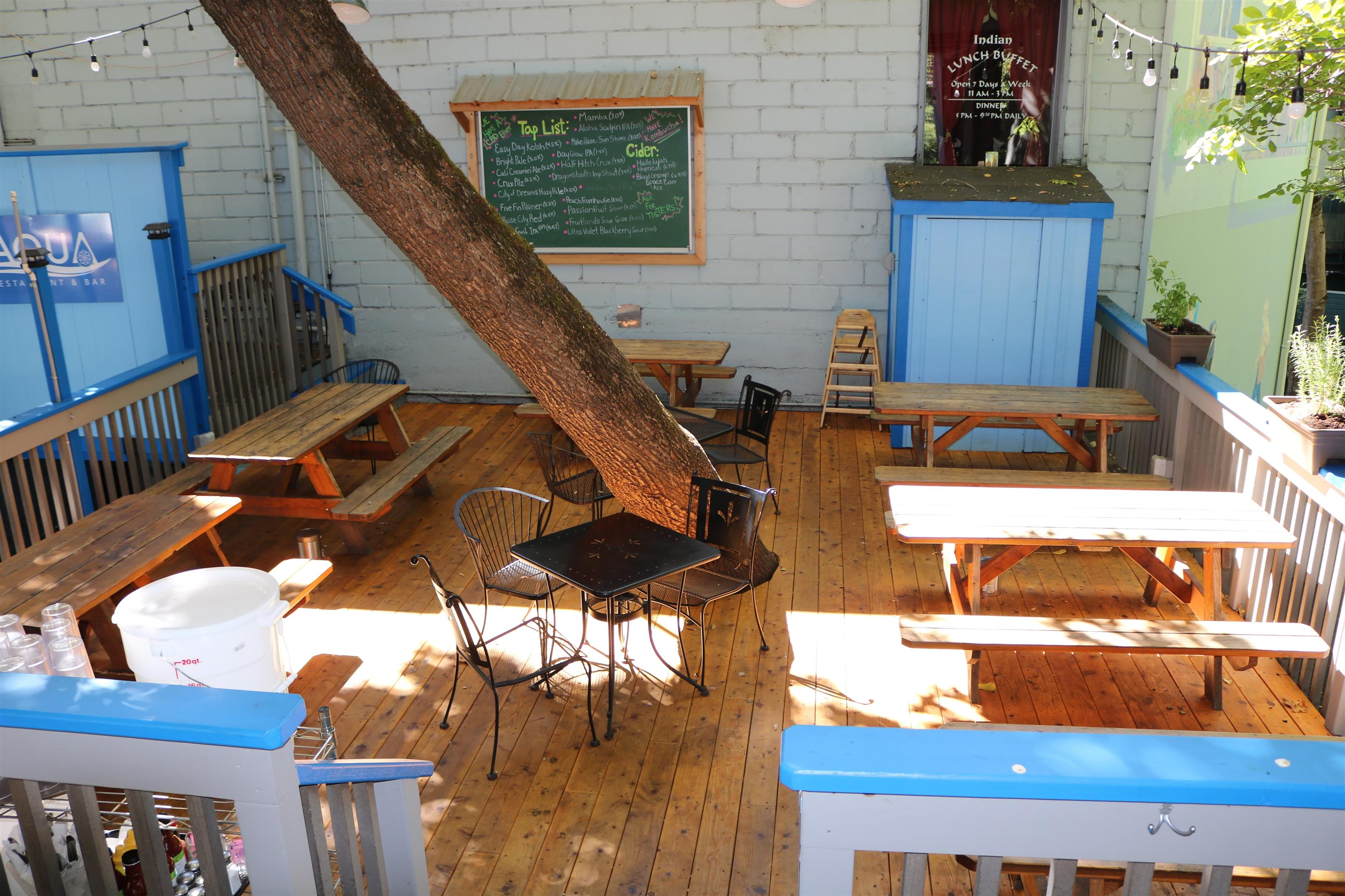Outdoor seating with wood bench picnick tables, wooden floor. Chalkboard tap list is on white brick wall.