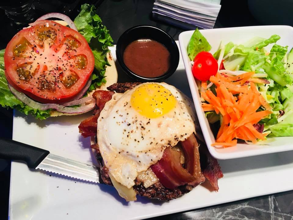 Open-faced burger with cheese, bacon, egg, tomato, lettuce, onion with side salad.
