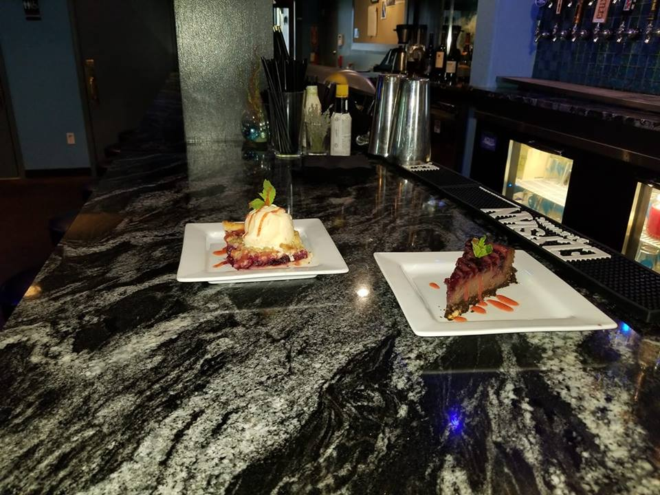 Two desserts on white plates on top of marble bartop.